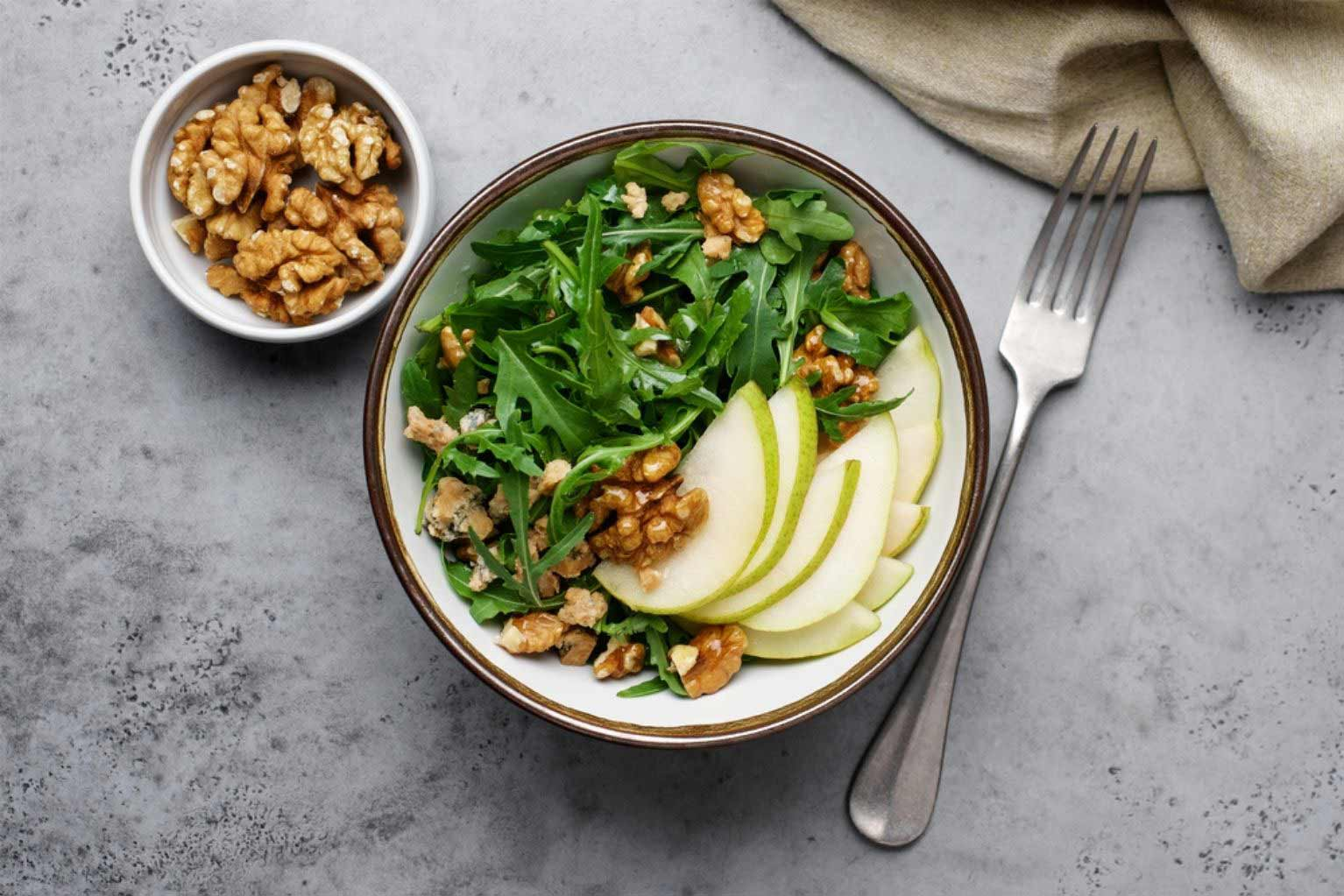 Salad with arugula, walnuts, cheese, and pears in a glass bowl next to a small bowl of walnuts and a fork.