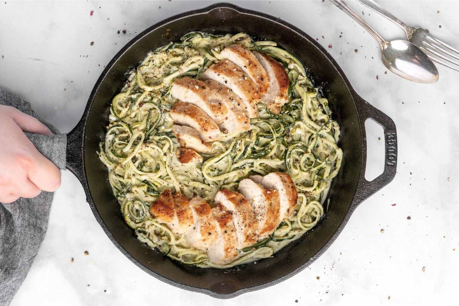 One skillet of zucchini noodles and chicken being held by a person over light gray counter tops.