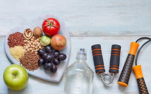 Healthy food on heart shaped board with water bottle and fitness gear