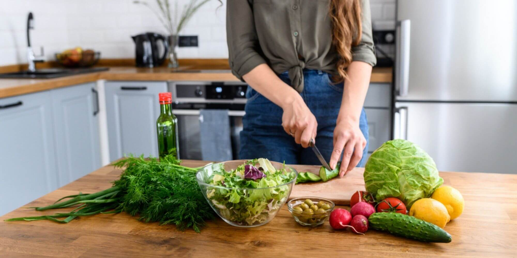 Woman slicing cucumbers on a wooden cutting board in a kitchen next to lettuce, olives, tomatoes, and lemons.