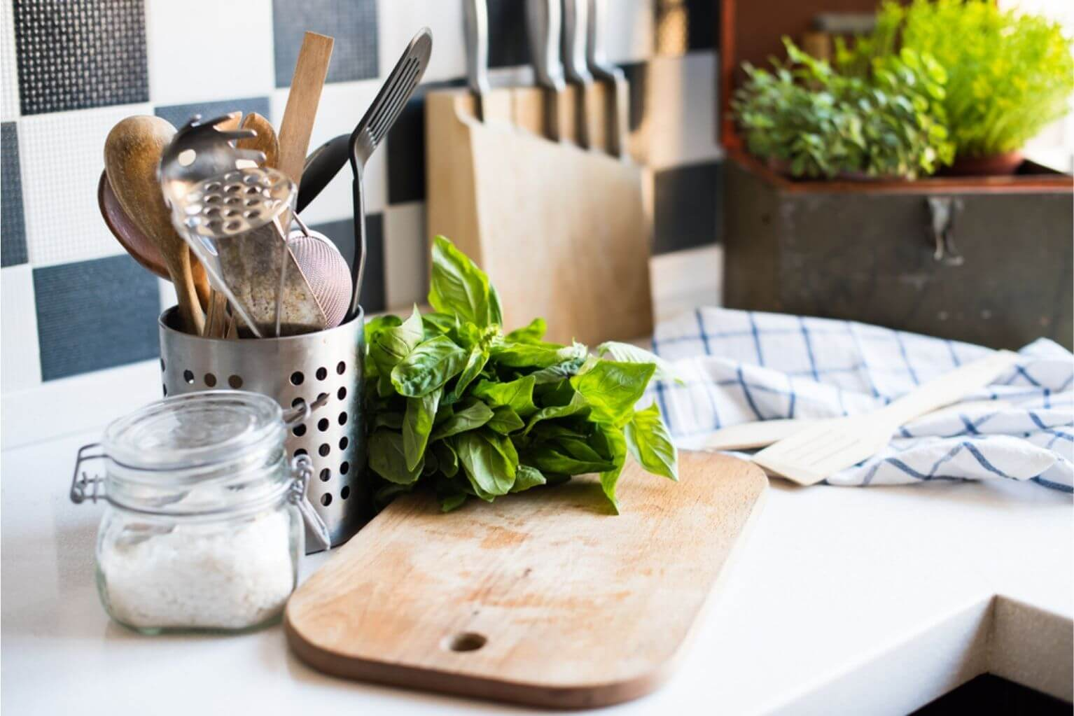 Salt and basil next to kitchen utensils and a cutting board on a white kitchen countertop