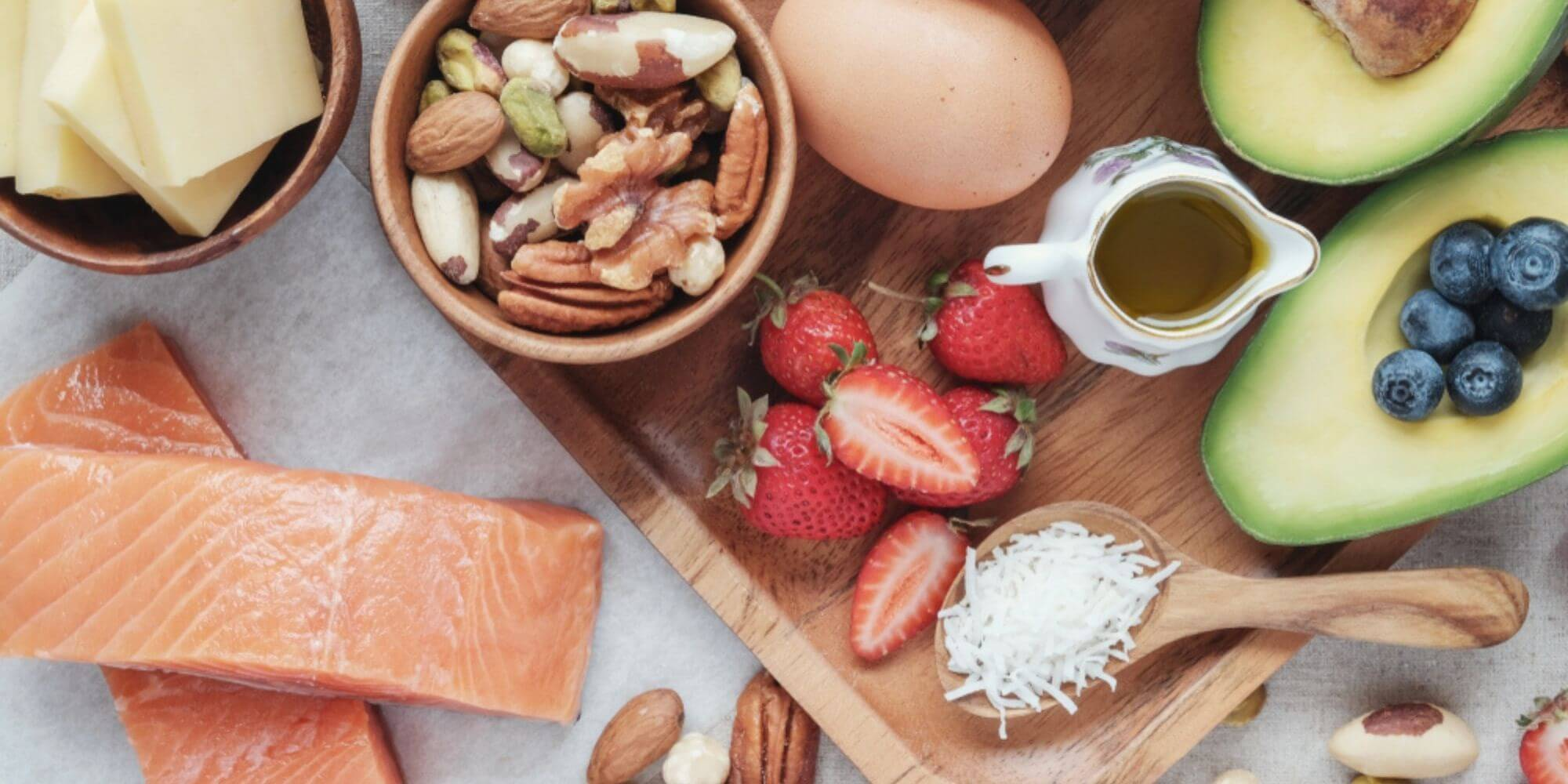 Aerial view of salmon, nuts, cheese, strawberries, eggs, avocados and coconuts on a wooden board.