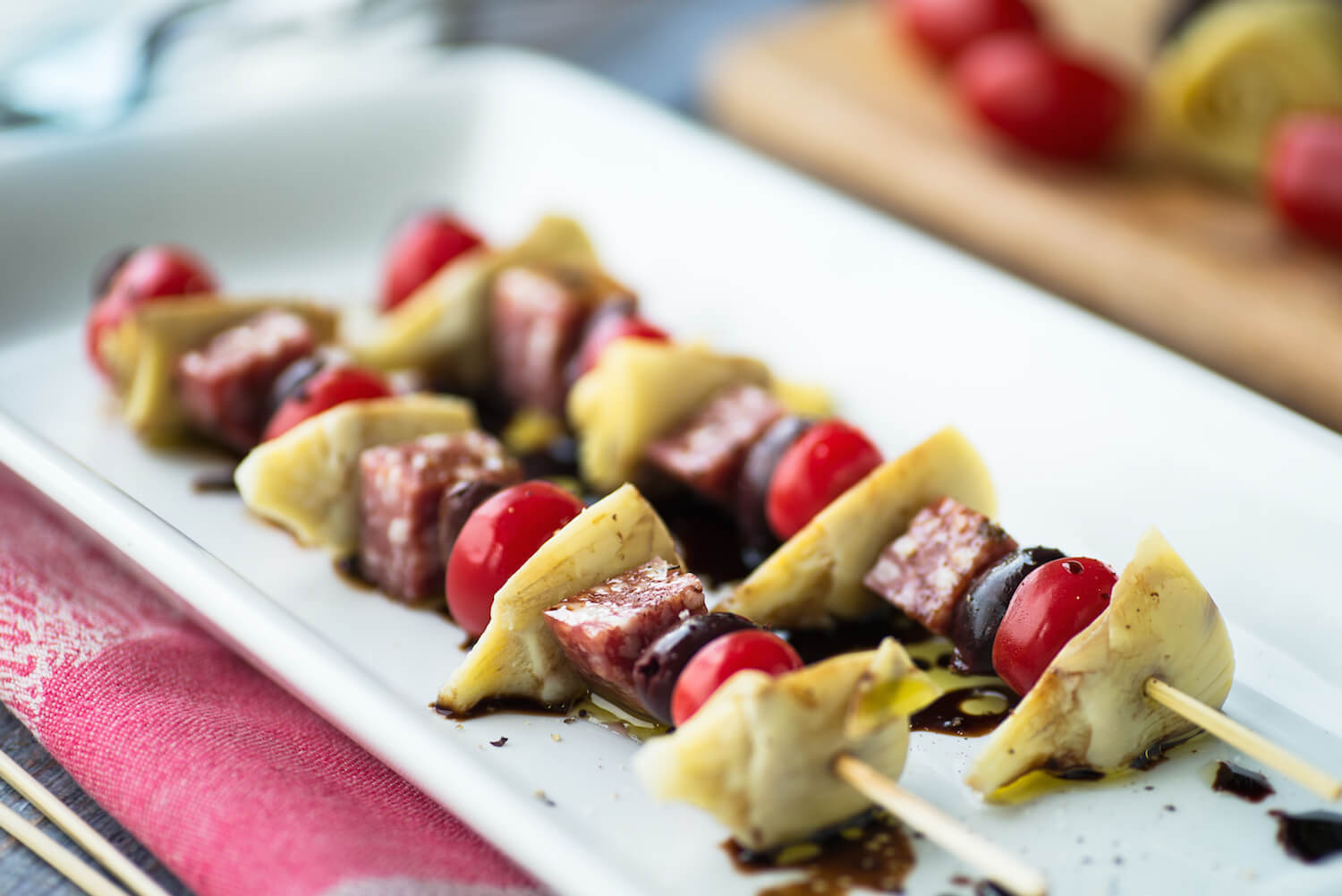 Antipasto kebabs with salami olives artichokes and tomatoes on a white plate