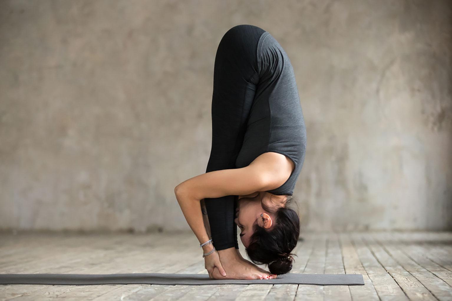 Young woman practicing the forward fold yoga pose