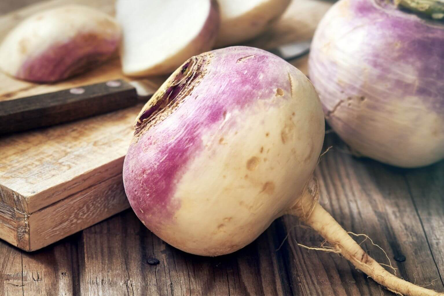 Three turnips next to a cutting board with a knife on top.