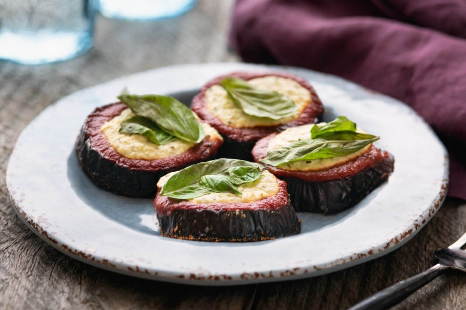 Four baked eggplant slices with ricotta and basil on a blue plate next to a maroon napkin and fork.
