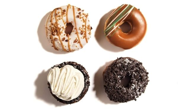 Four doughnuts laying next to each other against a white background all with different toppings.