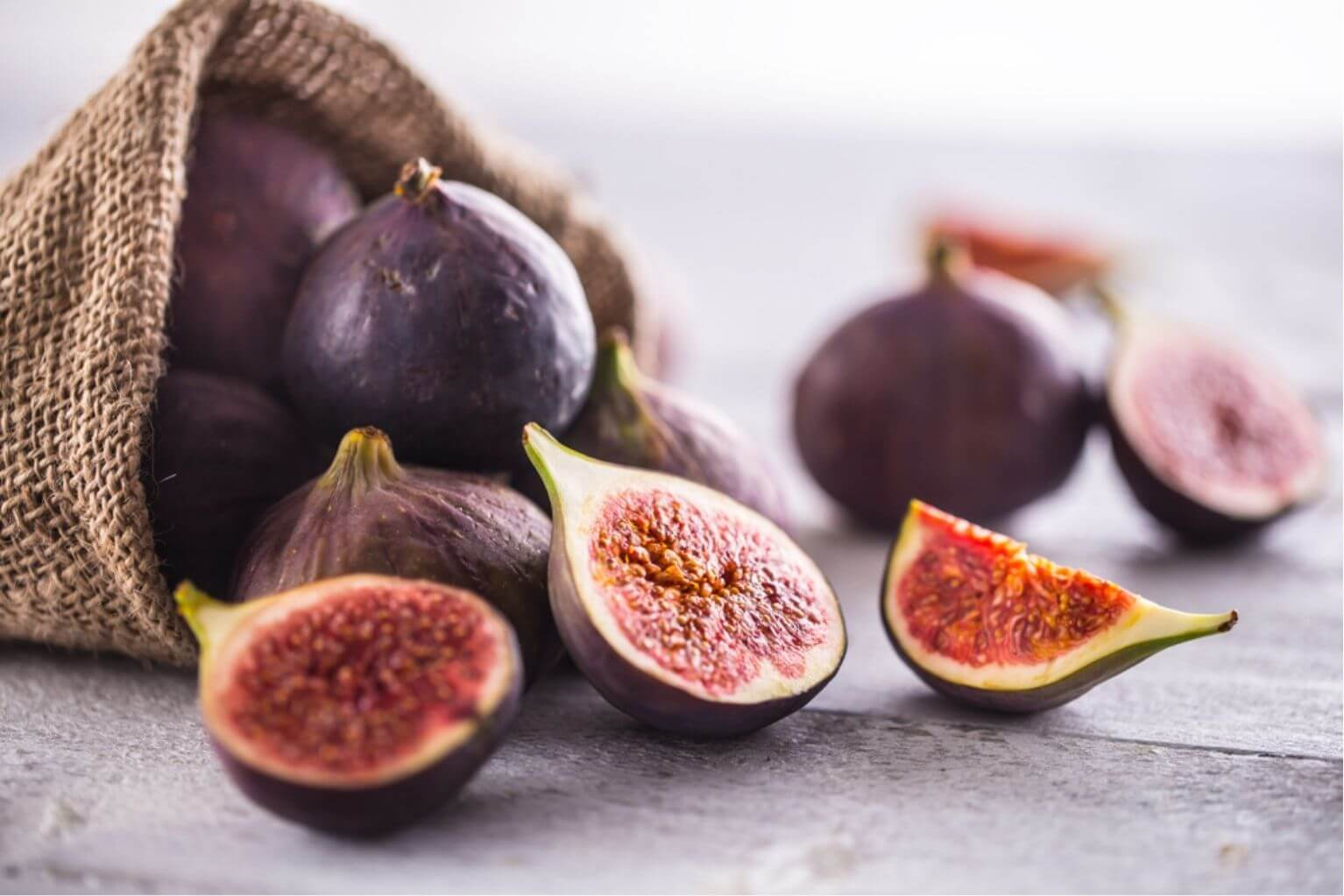 A burlap sack full of ripe figs over spilling onto a wooden table with three cut open figs in the front.
