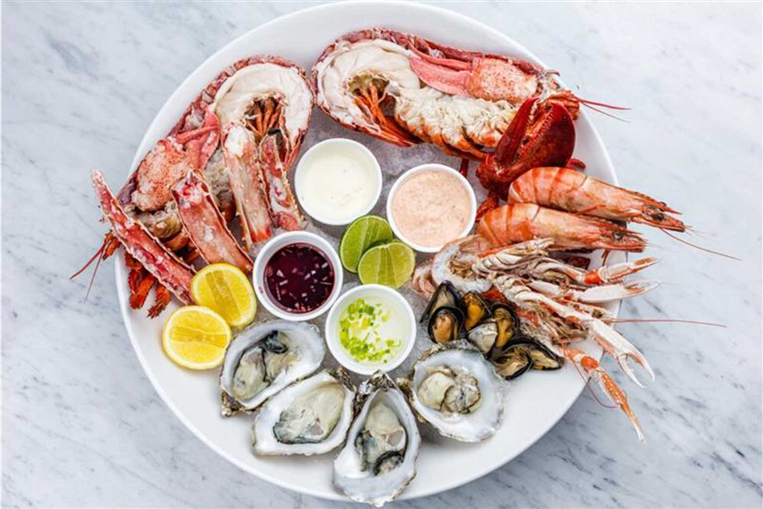 a fresh seafood plate full of oysters, shellfish, lobster, and mussels over ice with garnishes of lemon, lime and assorted dipping sauces