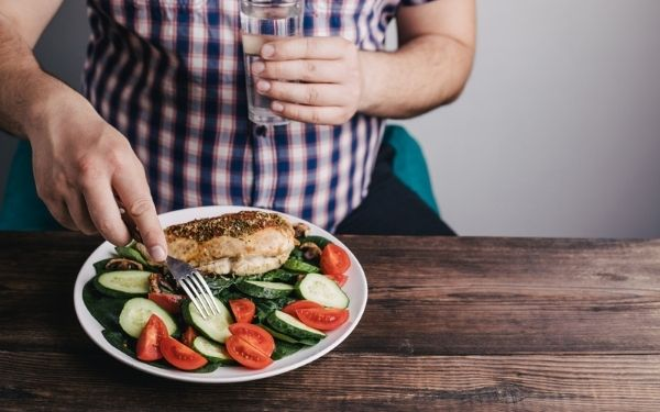 Man in a plaid shirt holding a glass of water and a fork that is stabbing a cucumber salad with chicken and tomatoes.