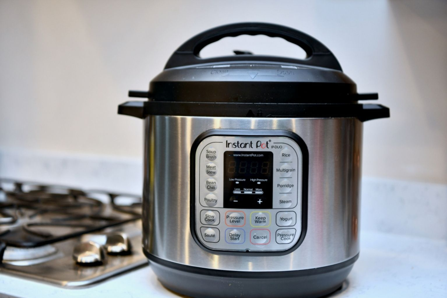 An instant pot on the kitchen counter next to the stove top