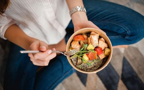 woman eating a bowl of salmon, bell peppers, and quinoa in a bowl with a fork in her hand