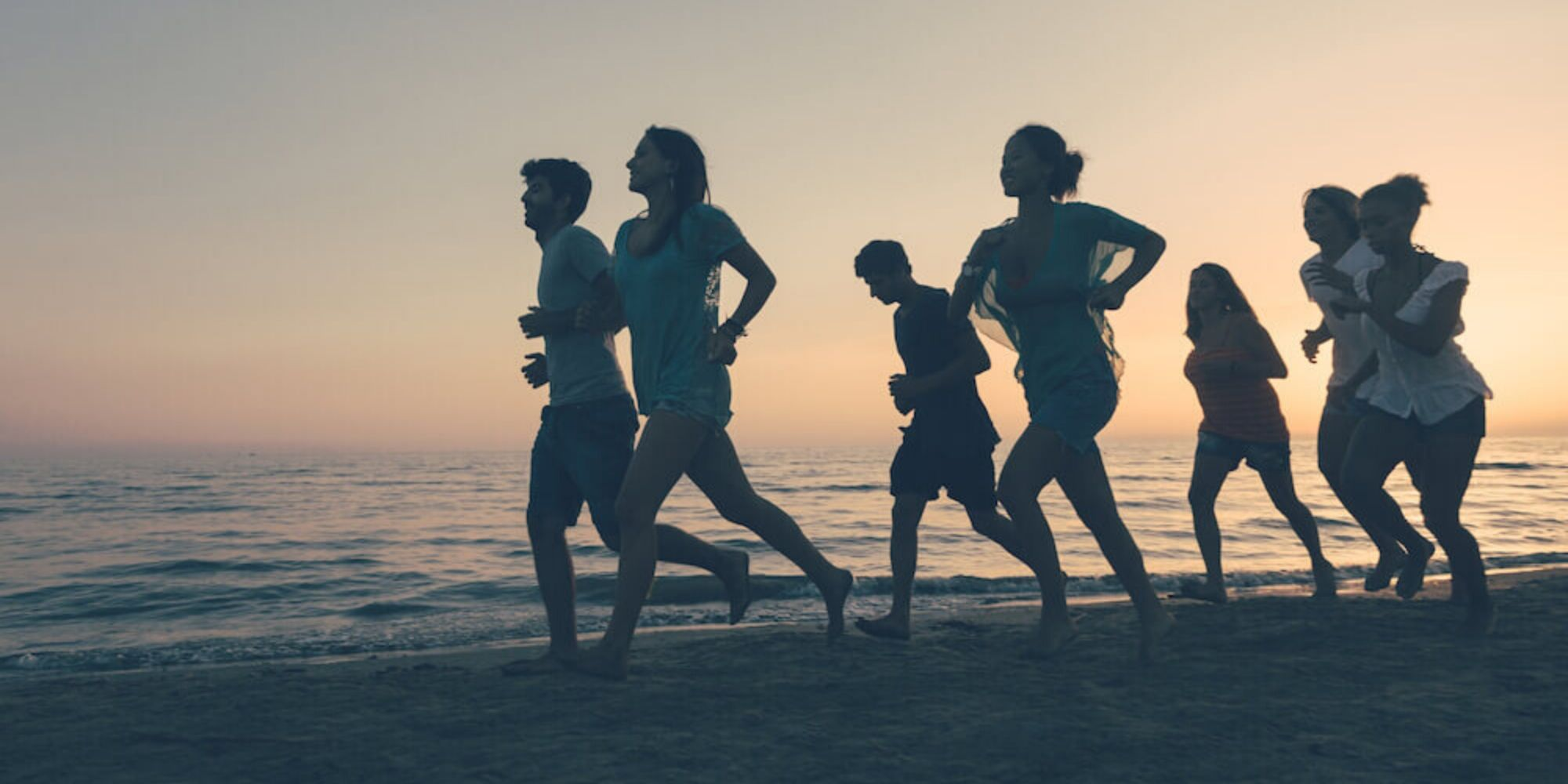 Group running together on a beach at sunset