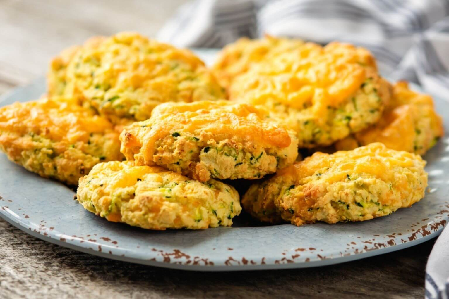 Grain-free cheddar and zucchini scones on top of a blue plate next to a blue and white stripped napkin.