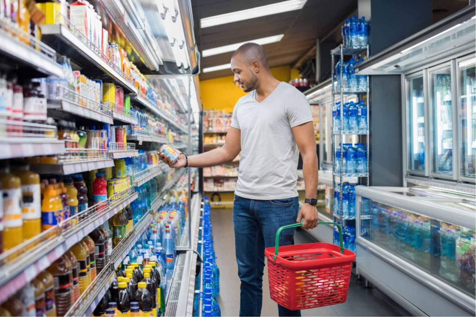 Man in a gray shirt is standing at the refrigerator at a grocery store holding a can of juice and a grocery basket.