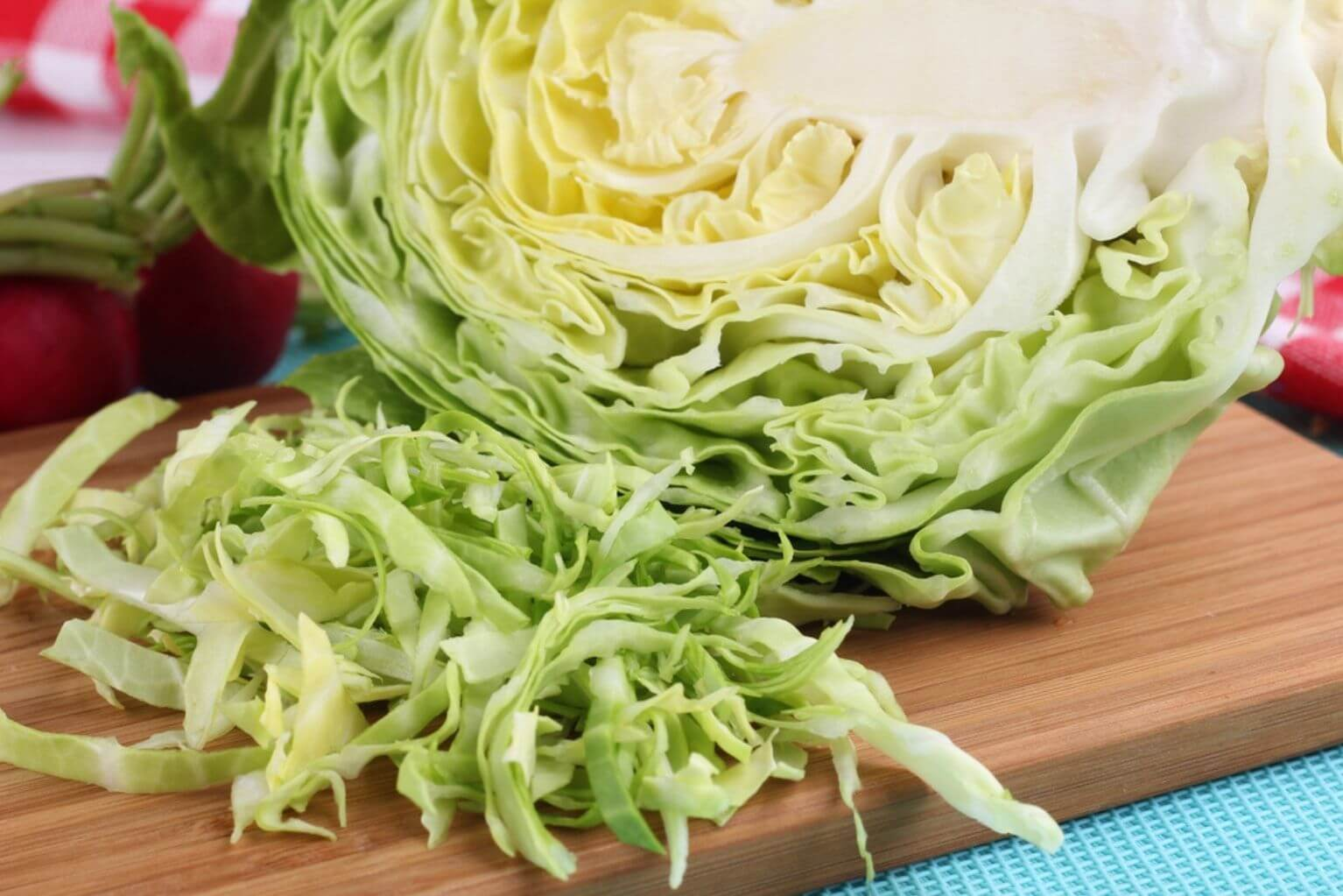 A head of cabbage on a cutting board lying next to shredded cabbage.