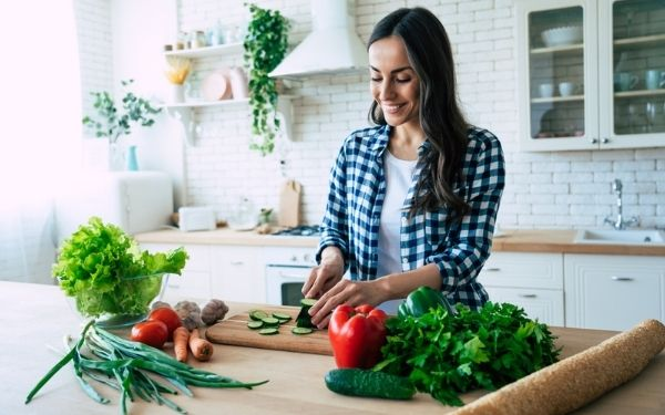 Young woman chopping vegetables on wooden cutting board in sunlit kitchen.