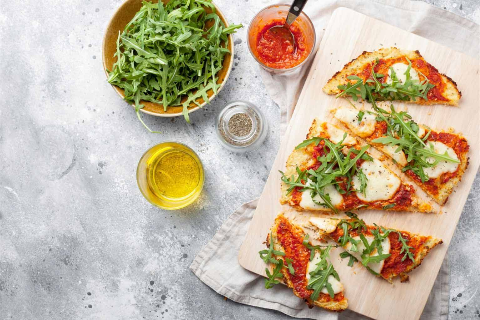 Mozzarella pizza with cauliflower crust on a wooden cutting board next to oil, pizza sauce, and arugula on a white table.