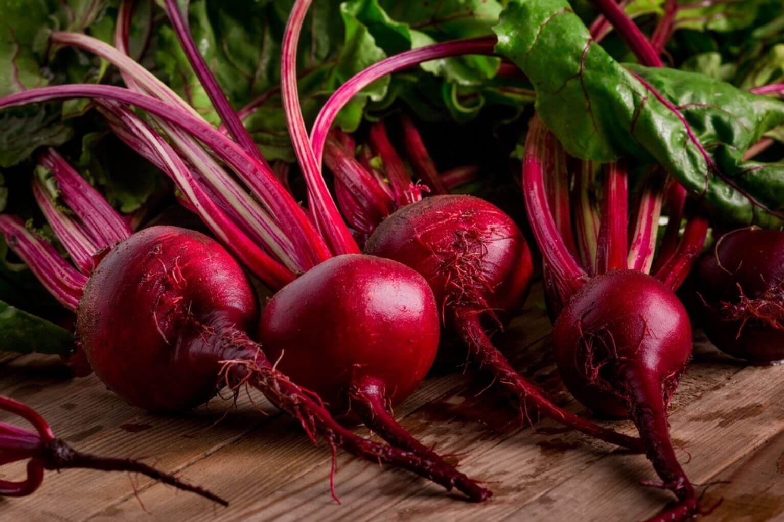 Four beets with their leaves and roots attached on top of a wooden table.