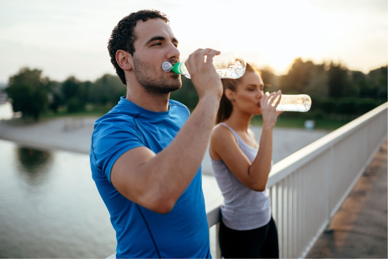 Man and woman happy and drinking water on bridge after workout
