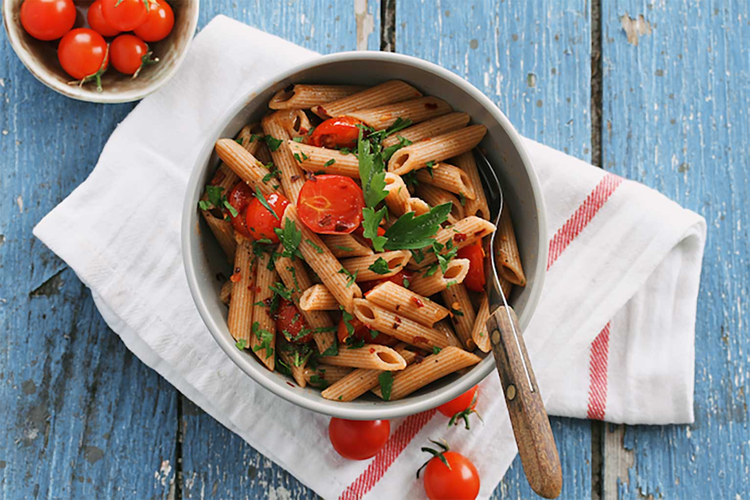 Penne arrabbiata pasta with tomatoes basil and parsley in a bowl