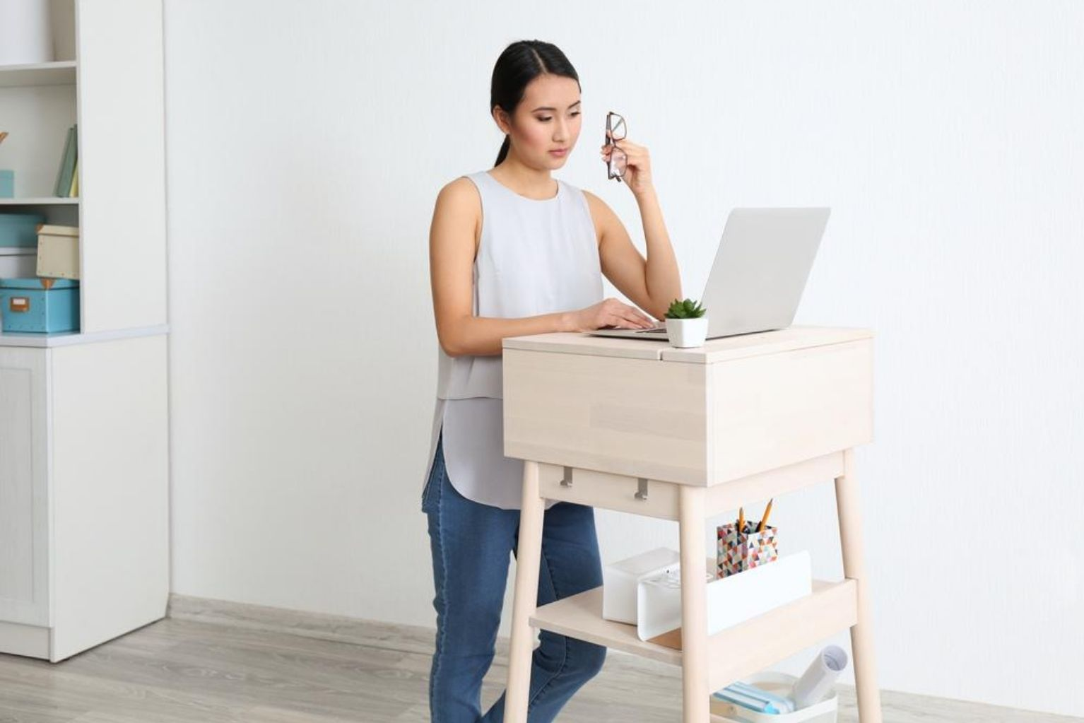 Woman at a stand up desk in her living room at her house working on a laptop