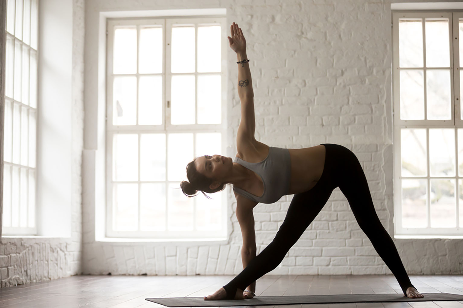 Young woman practicing the triangle yoga pose