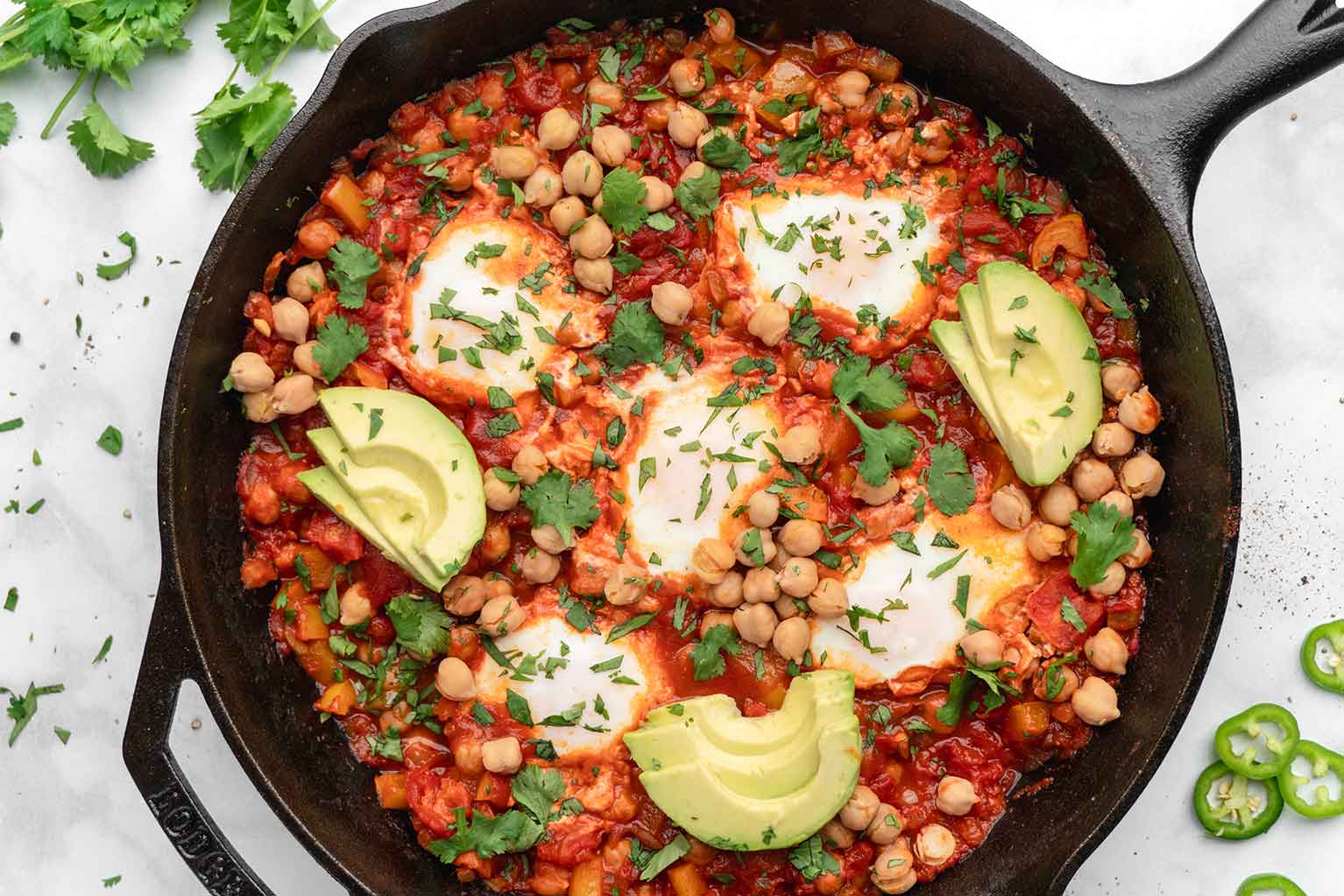 Shakshuka-with-eggs-chickpeas-avocado-and-tomato-sauce-in-cast-iron-skillet