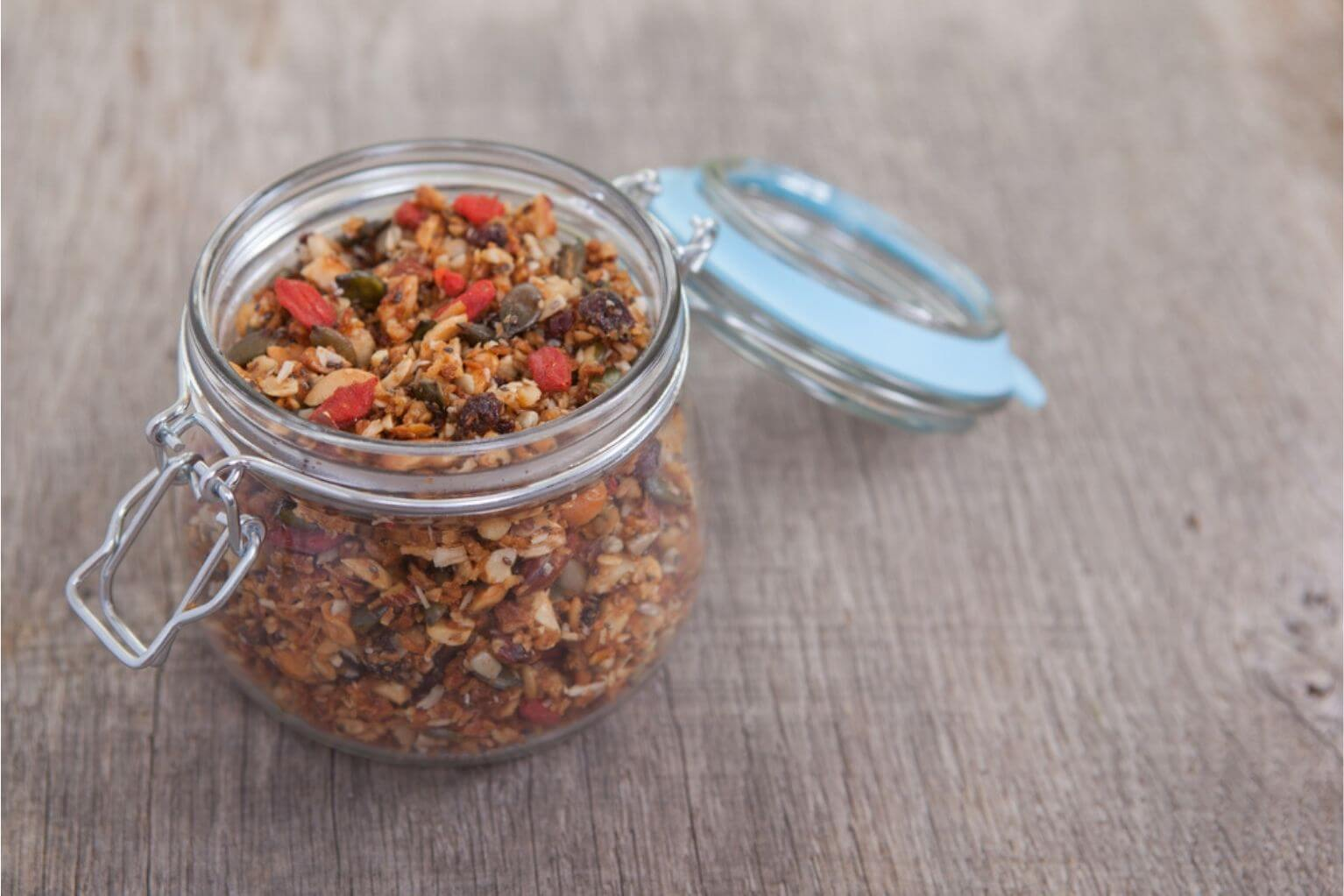 Grain-free granola made with mixed nuts, seeds, raisins, coconut flakes, chia, and coconut seeds in a glass jar on a wooden table.