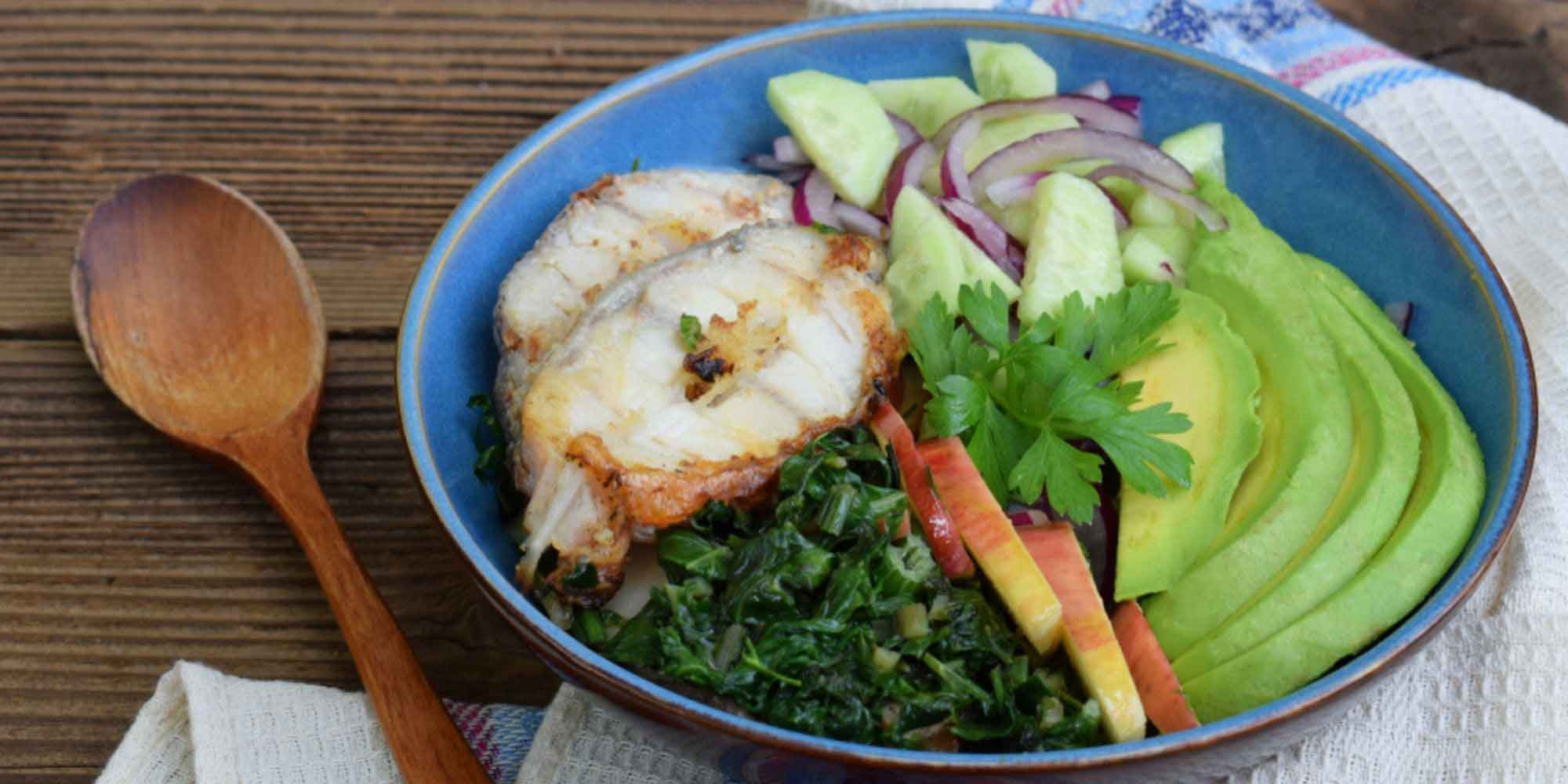 Wooden spoon, blue plate holding AIP Diet meal of grilled chicken, kale, cucumbers, apples, avocado, red onion, and parsley.