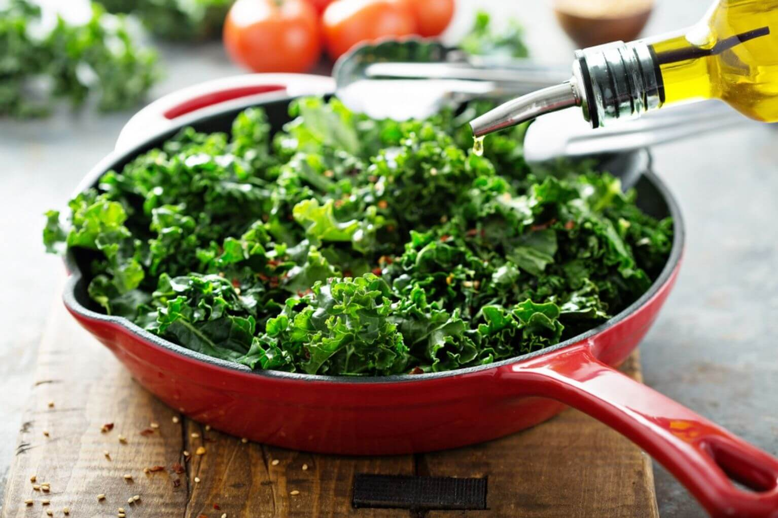 Red skillet filled with kale on top of a wooden board being drizzled with olive oil.