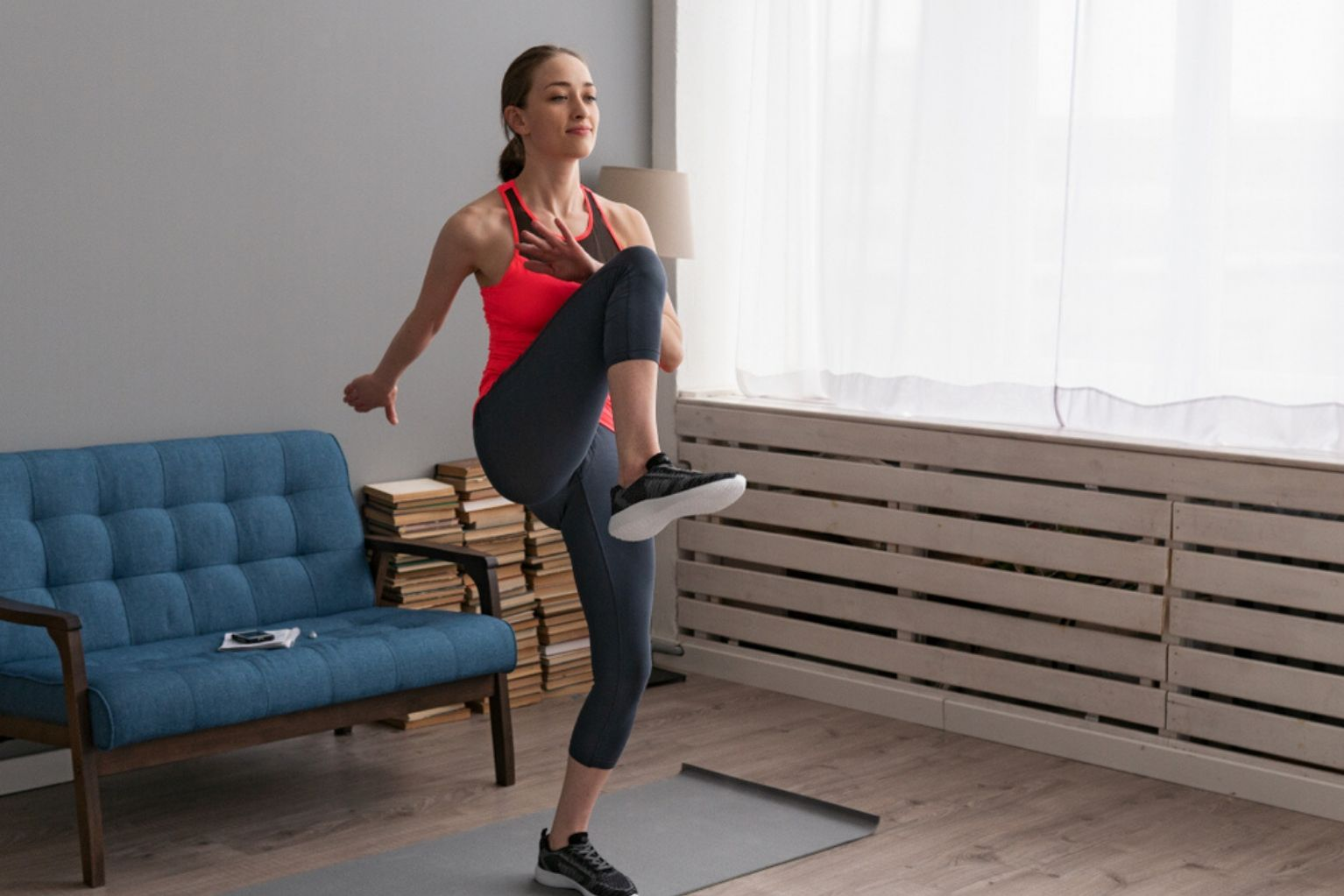 Young athletic woman doing high knees exercise in her home