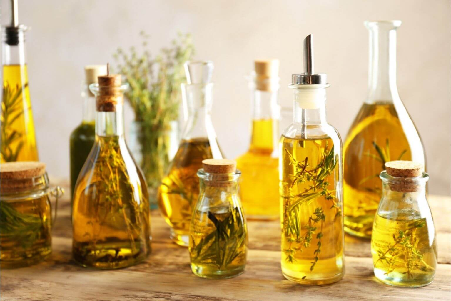 Many bottles of herb infused oil on a wooden table.