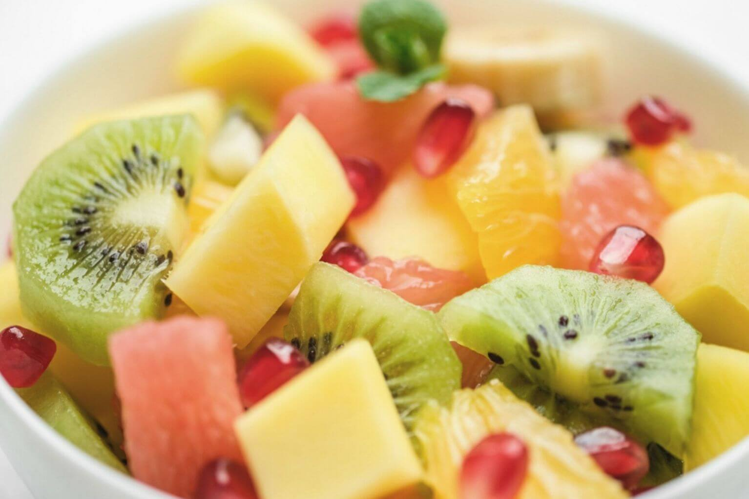 fruit bowl with diced kiwis, grapefruit, oranges, mango, and pomegranate