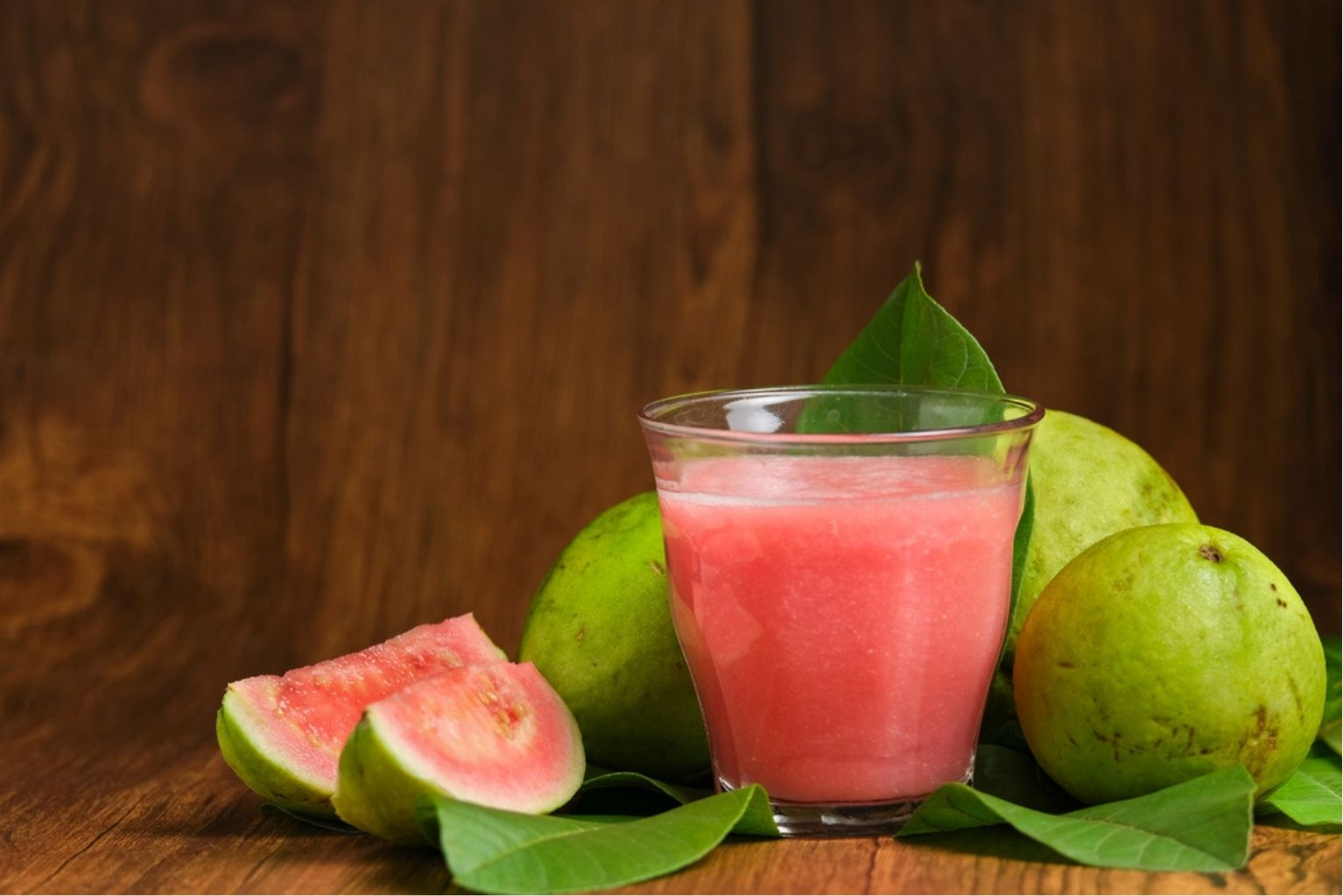 Clear glass filled with pink guava juice next to three guava fruits and two slices of guava on a brown wooden table.