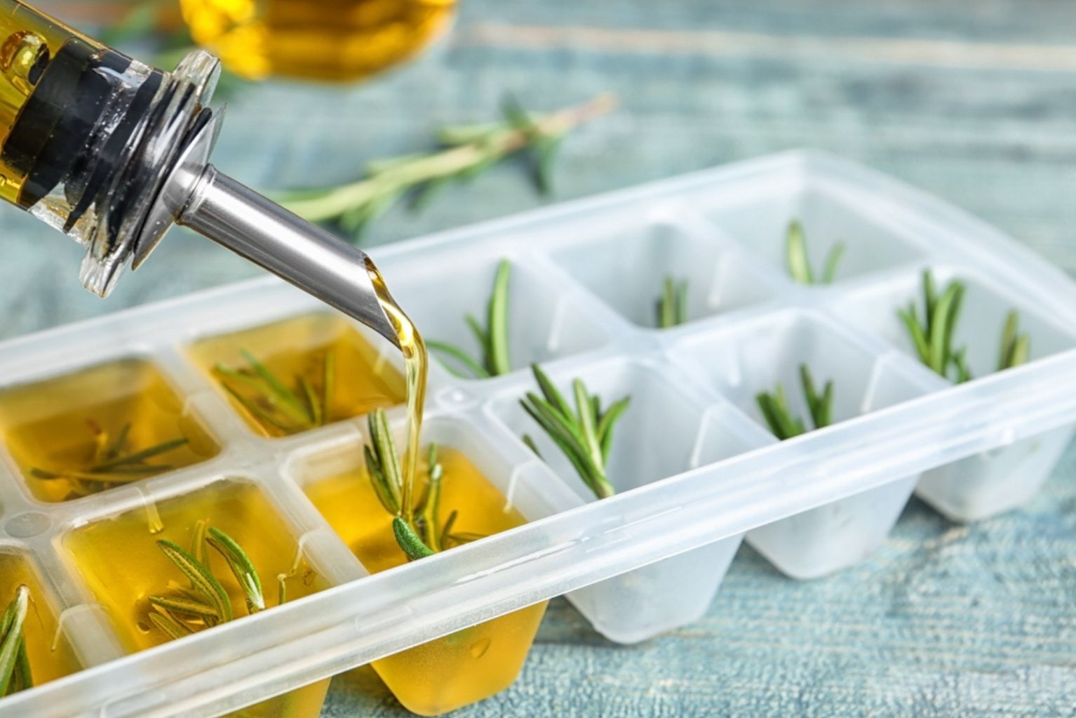 Olive oil being poured into an ice cube tray with rosemary in it.