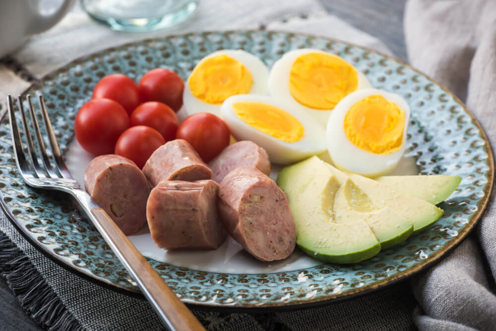 Breakfast bento with chicken sausage, egg and avocado