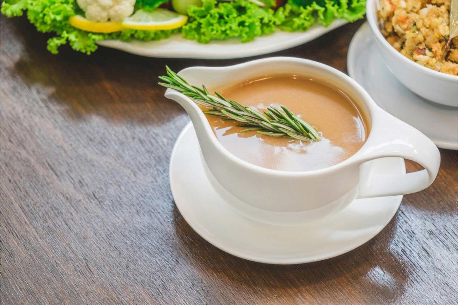 White ceramic gravy boat filled with gravy and a stem of rosemary on a wooden table.