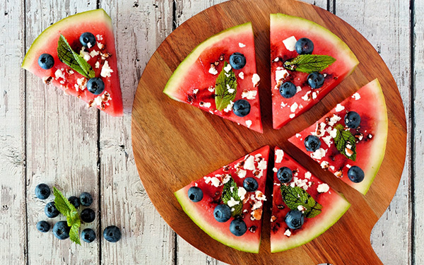 Watermelon with blueberries, mint feta cheese and balsamic glaze on a wooden board