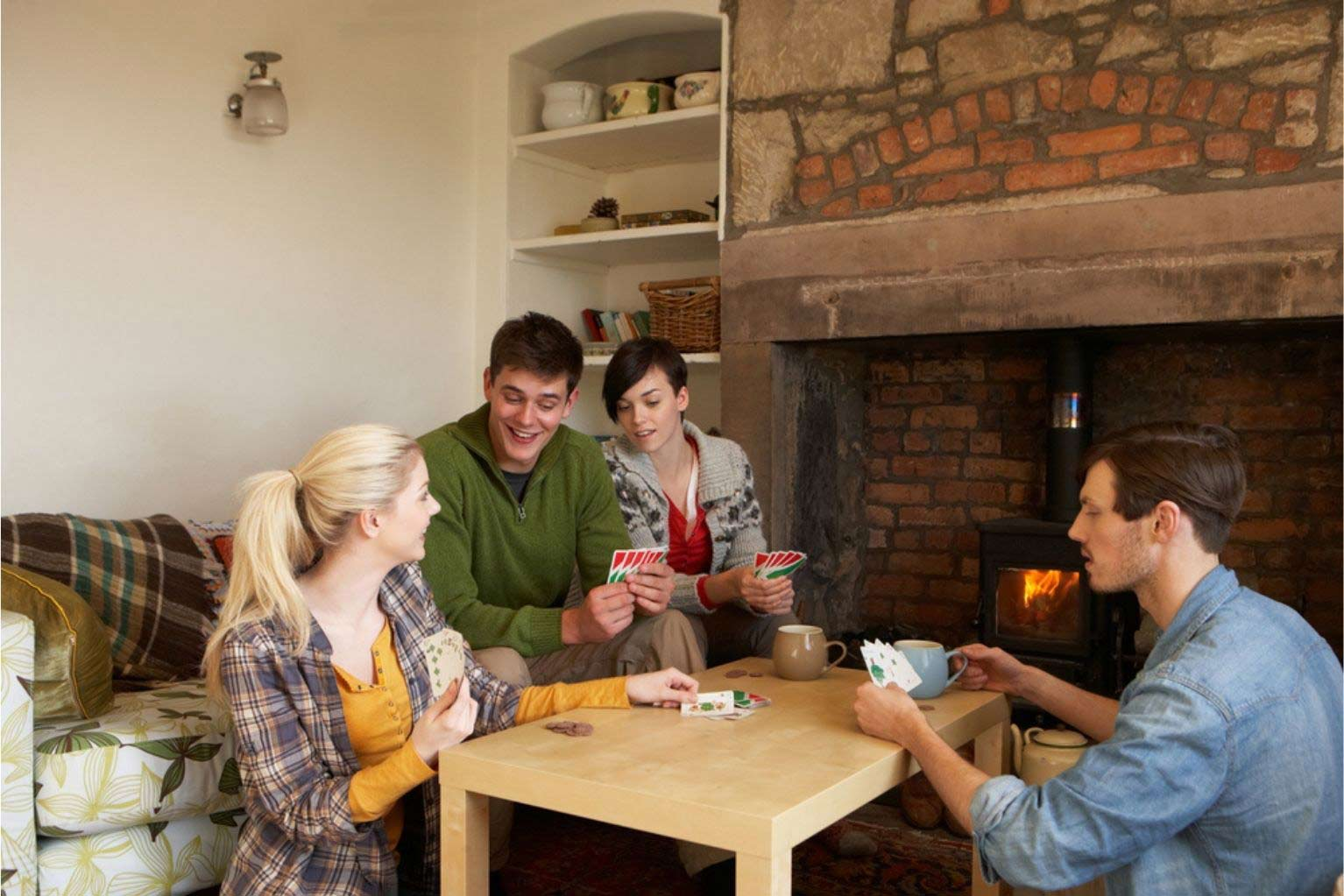 A group of people playing cards around a coffee table next to a fire place inside a house.