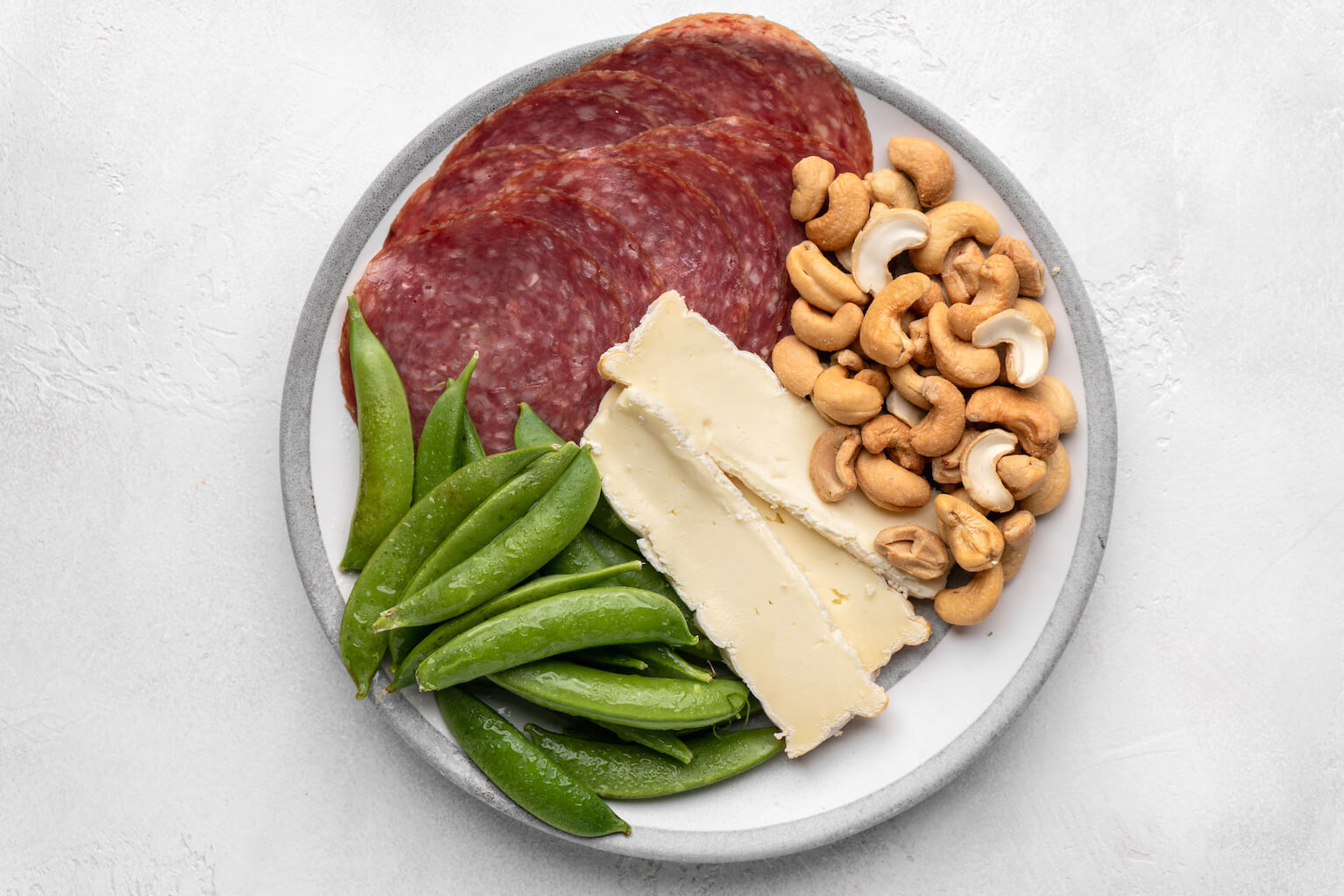 healthy cheese plate with salami snap peas and cashews