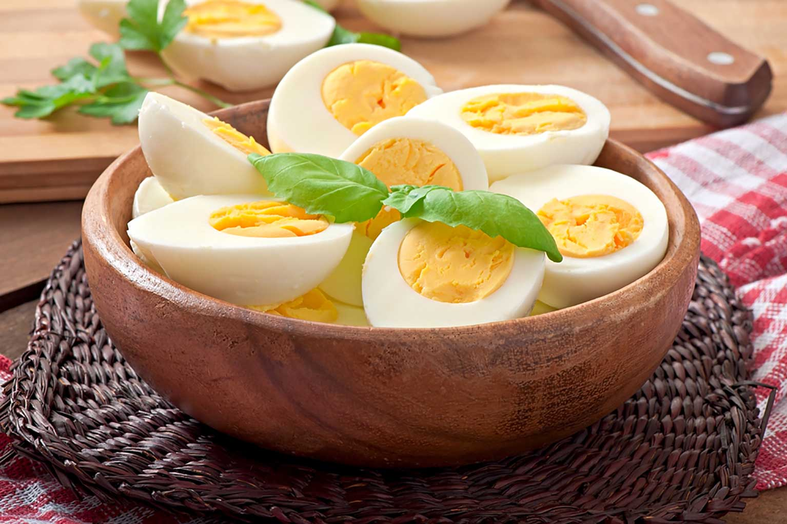 wooden bowl full of hard-boiled eggs with garnish