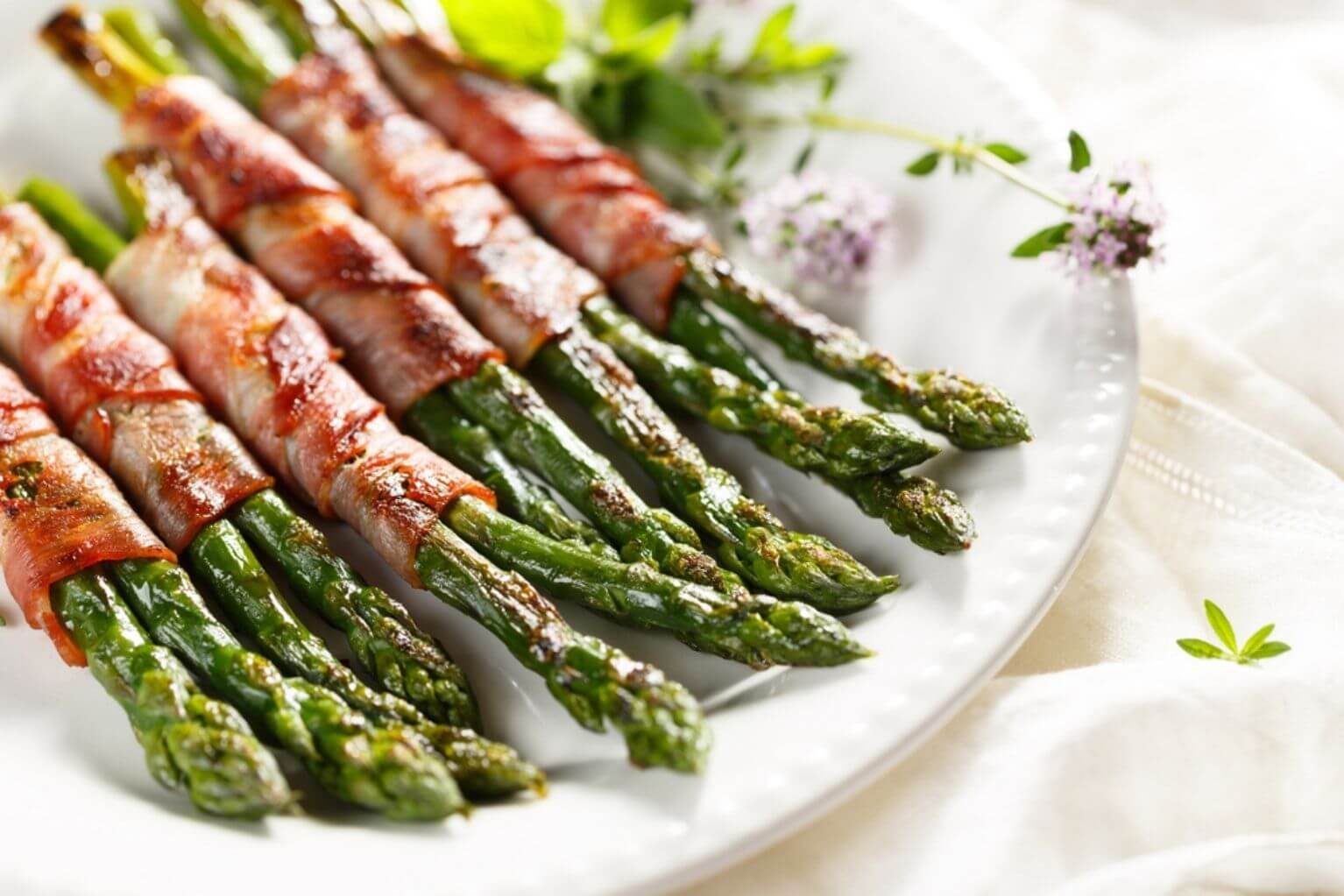 Bacon-wrapped asparagus on a white plate with herb garnishes on a white table cloth.