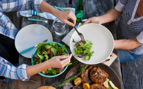 two people sitting at a table scooping salad onto white plates