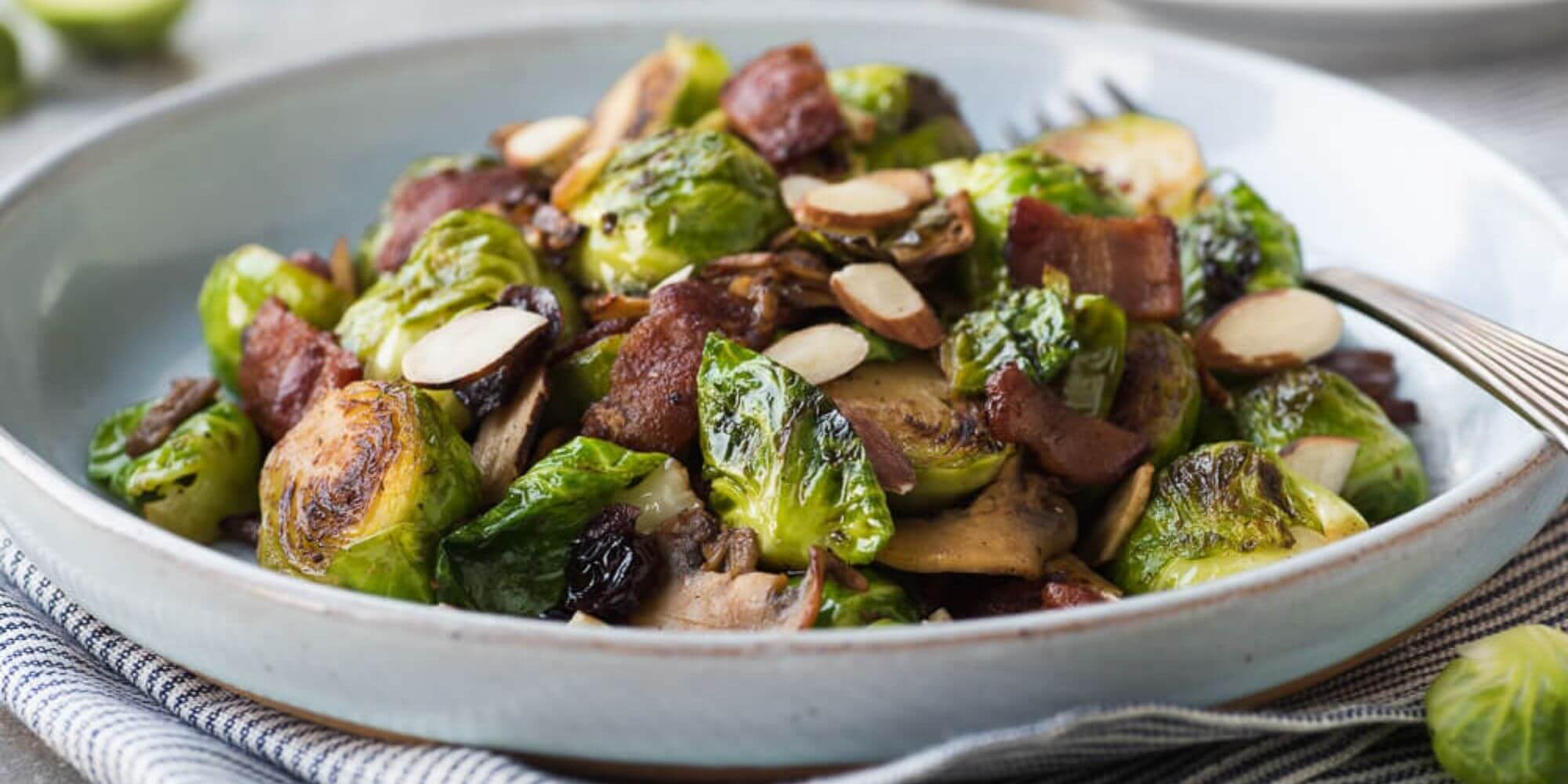 Bacon and brussels sprout hash in a gray bowl with a fork sitting on top of a napkin.