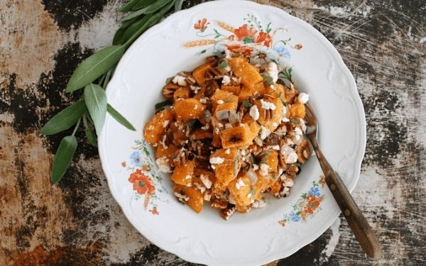 Butternut squash salad with feta cheese in a white bowl on a wooden table with a fork.