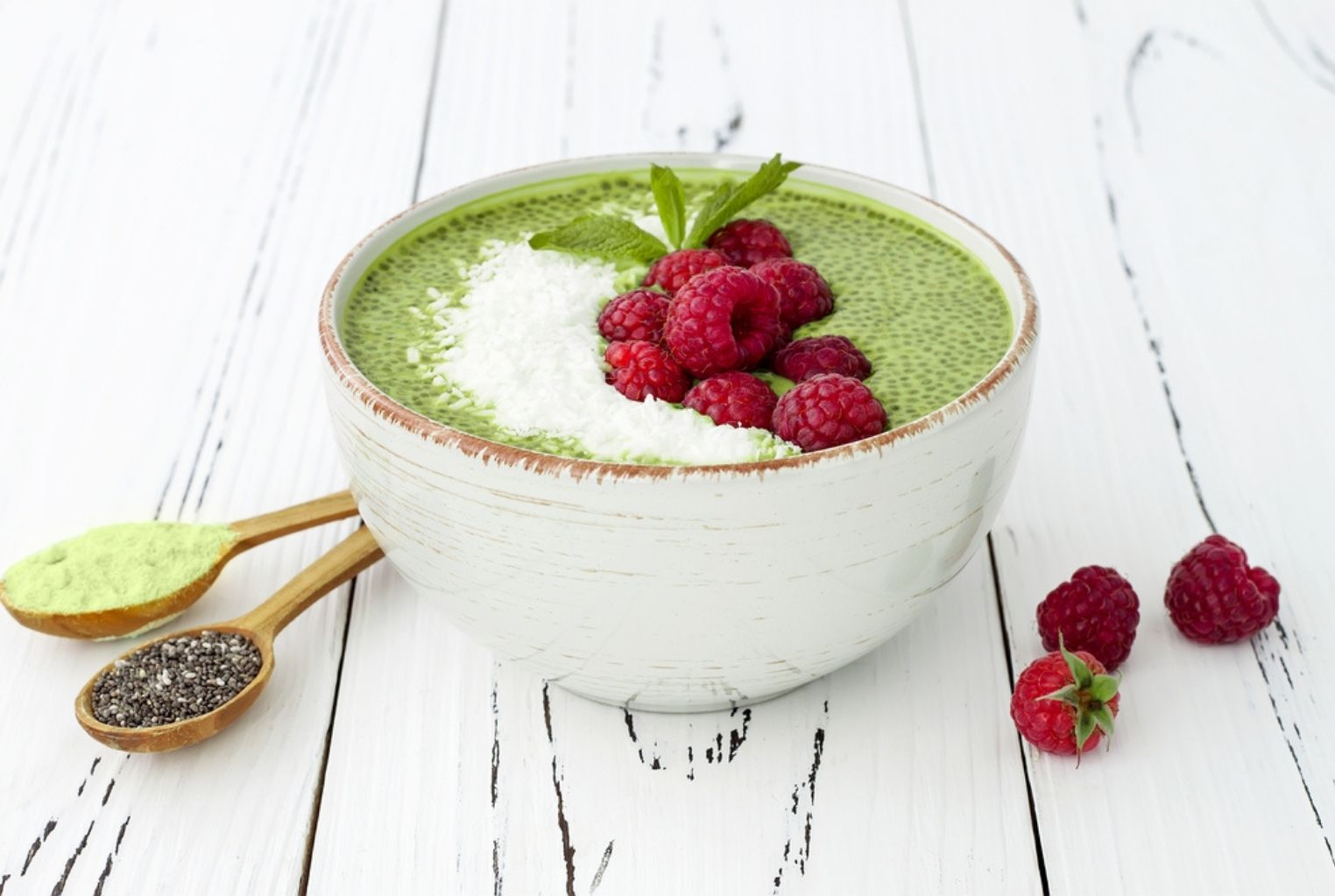 Bowl of a green matcha and chia smoothie topped with shredded coconut and whole raspberries.