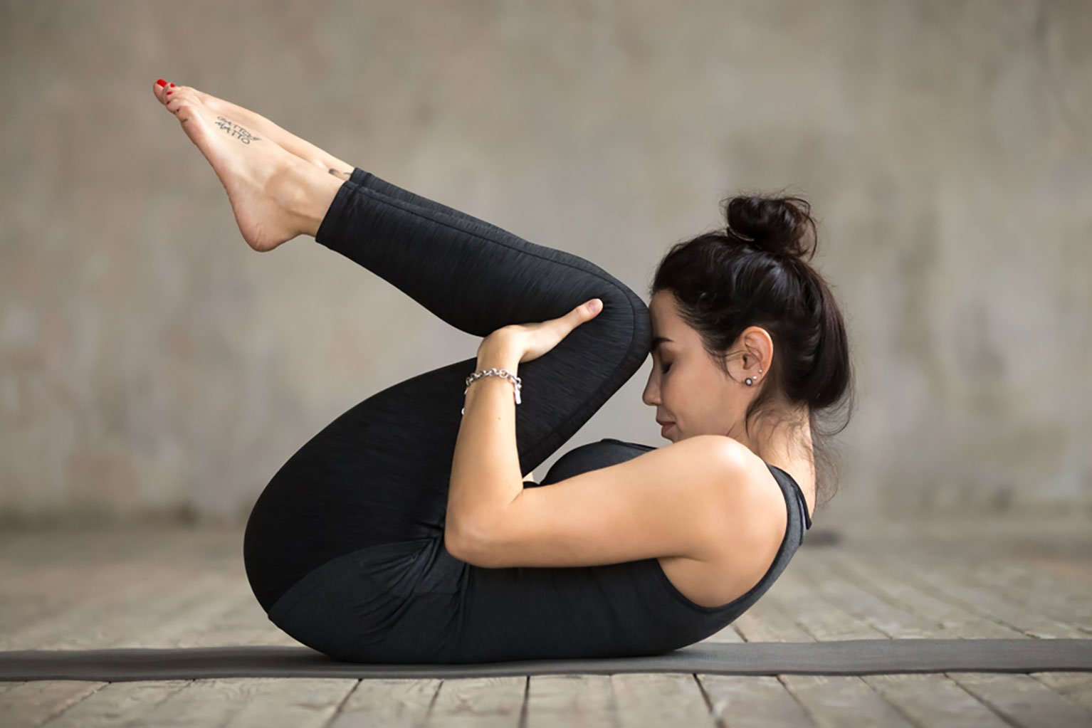 Young woman practicing the knees to chest yoga pose