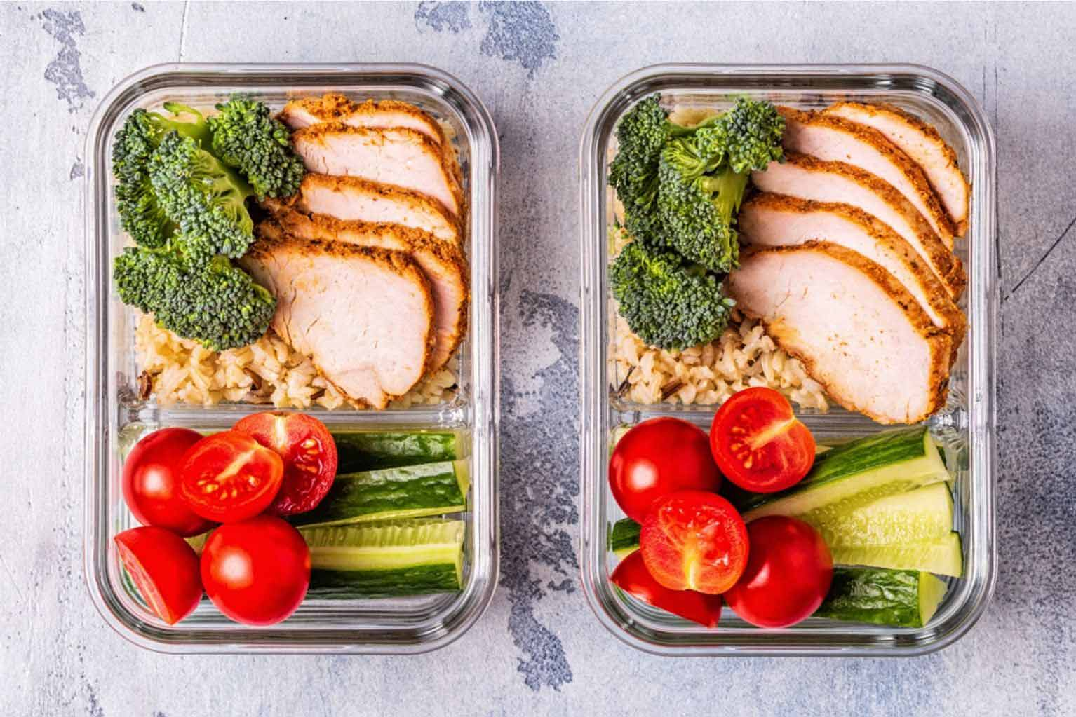 Two glass containers filled with chicken, broccoli, brown rice, tomatoes, and cucumbers