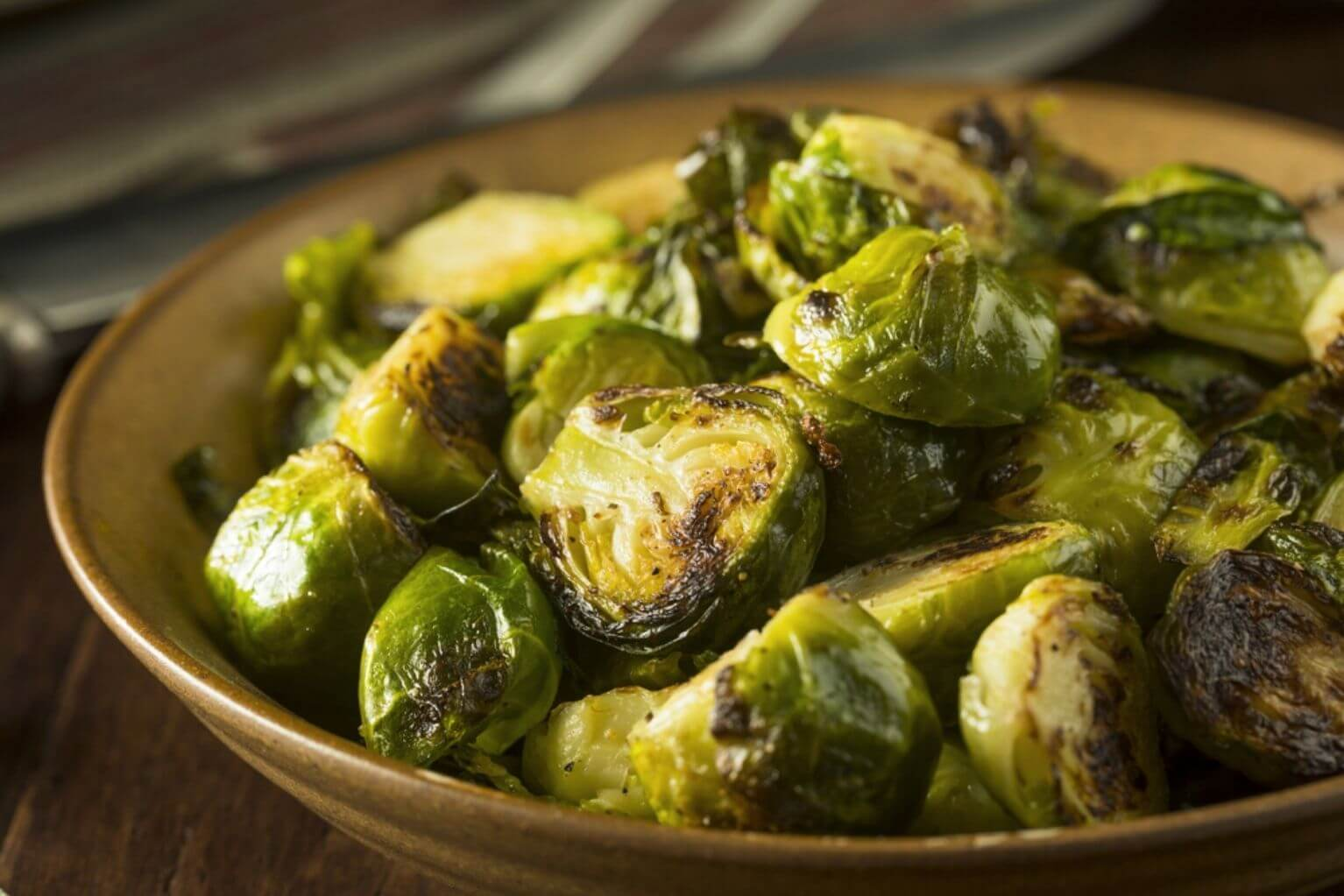 Tan bowl full of cooked brussel sprouts that are cut in half.